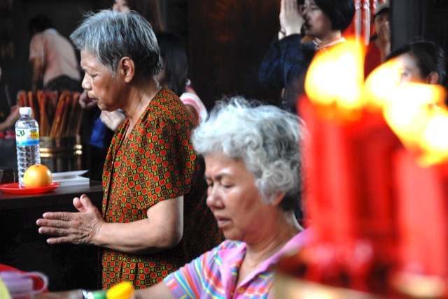 Older women pray by candles at Long-shan temple Buddhismus