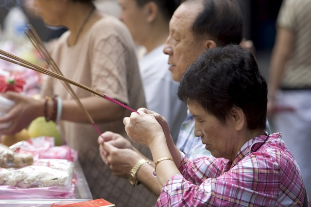 Longshan Temple, people praying, reading and offering incense. Taiwan