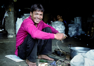 A man smiles for the camera inbetween his job of separating cables at a recycling plant in Bangkok.