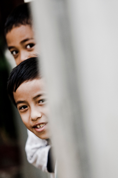 A young boy peeks outside the door of his home in Joglo, Jakarta.