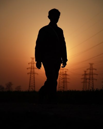 A worker is silhouetted against the setting sun as he finishes another day of work. Shunyi District, Beijing