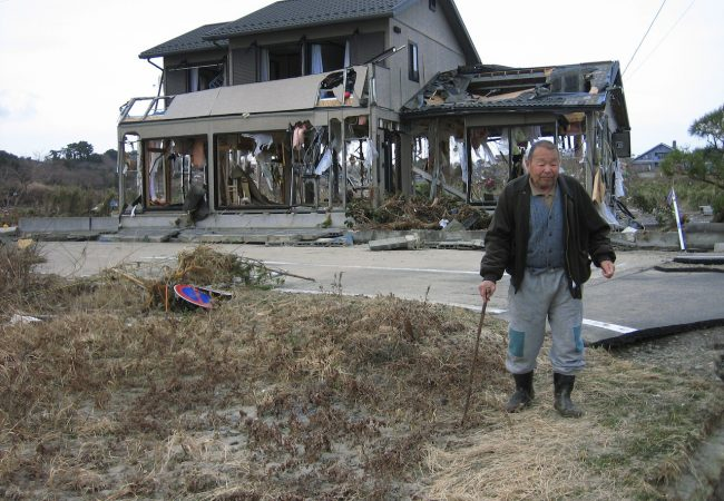 RS10040_Man stands in front of gutted house - Sendai Takeyama area-scr
