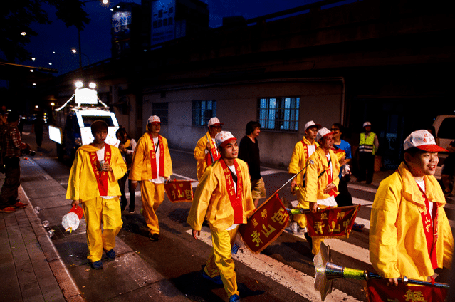 men in taiwan marching in street wearing yellow in religious parade at night