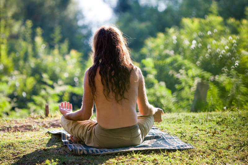 american buddhism white man with long hair and not shirt sits outside meditating