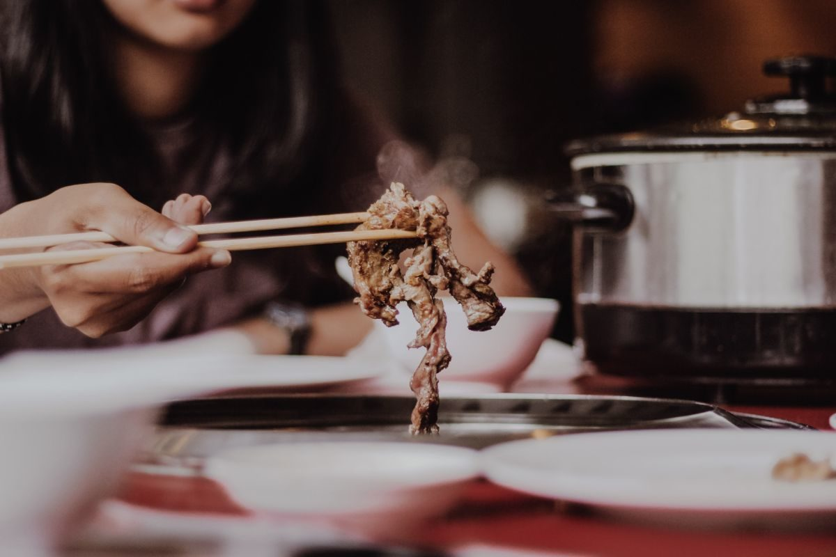 woman eating beef with chopsticks at a table showing racial reconciliation