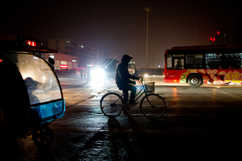 Man riding a bike on street in Asia at night with emotional feeling of lessons on spiritual warfare