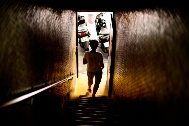 man in taiwan walking dark stairwell into bright daylight with motorcycles in sights showing spiritual warfare