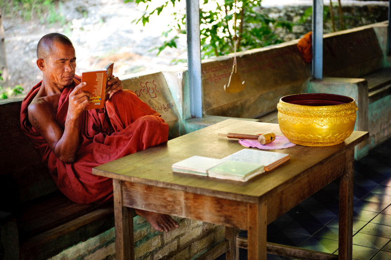 buddhist man in orange robe sits reading resources on buddhism